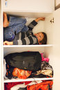 Hide and seek funny boy playing hiding in a closet Stock Photos