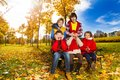Hide and seek game friends surprise guess who action with boys hiding girls face with palms in autumn park Stock Photos