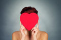 Hiding face behind red heart young woman her a Stock Image