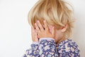 Hiding face with hands little girl closeup on white Royalty Free Stock Photos