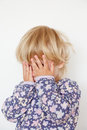 Hiding face with hands little girl on white Stock Photography