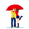 Hiding kiss under umbrella shy couple big red kissing romantically in love on a rainy day Stock Photo