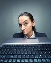 Hiding young caucasian businesswoman behind laptop Stock Photos