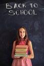 High achiever schoolgirl standing with books against blackboard