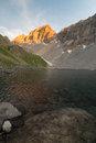High altitude alpine lake in idyllic land once covered by glaciers. Majestic rocky mountain peak glowing at sunset. Wide angle ver Royalty Free Stock Photo