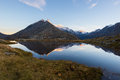 High altitude alpine lake in idyllic land with reflection of majestic rocky mountain peaks glowing at sunset. Wide angle view on t