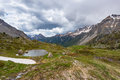 High altitude alpine pond in extrem terrain rocky landscape once covered by glaciers. Dramatic stormy sky and snowcapped mountain Royalty Free Stock Photo