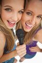 High-angle shot of two happy young beauty singing Stock Photo