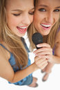 High-angle shot of two happy young blonde singing Stock Photo