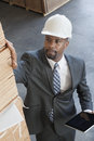 High angle view of african american male contractor inspecting wooden planks while holding tablet pc Royalty Free Stock Photo