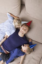 High angle view of father and children with artificial mustache and party hat sleeping on sofa bed Stock Photo