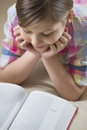 High angle view of girl reading book at home Royalty Free Stock Images