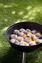 High angle view of glowing hot charcoal coals in a small portable barbecue standing on grass in preparation for cooking a healthy Royalty Free Stock Photos