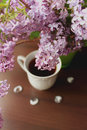 High angle view of lilac branch and cup of tea