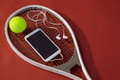 High angle view of mobile phone with in-ear headphones and ball on tennis racket Royalty Free Stock Photo