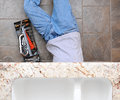 High angle view of a plumber laying under a kitchen sink man is unrecognizable with a tool box next to him Royalty Free Stock Image