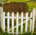High angle view of the white wooden fence protecting the entrance to the field on a sunny day Royalty Free Stock Photo