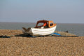 High and dry a small dingy on the pebbles of southwold beach Royalty Free Stock Photo