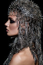 High fashion beauty model with metallic headwear and dark makeup and blue eyes on black background Royalty Free Stock Photo