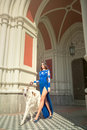 High fashion shot of elegant woman with dog in long blue dress Royalty Free Stock Photo