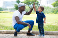 High five image of a modern father giving a hi his little son in the park Stock Photography