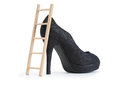 High heel wooden ladder near black female shoe with on white background Stock Photo