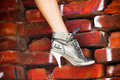 High heels sneakers woman leg in heel on red brick wall Stock Photography