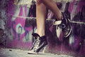 High heels sneakers woman legs in heel in front graffiti wall Stock Images