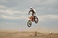 High Jump through the hill lands MX racer Royalty Free Stock Photo