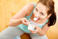 High key portrait young caucasian woman eating yogurt at home smiling Stock Photos