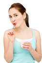 High key portrait young caucasian woman eating yogurt isolated smiling Stock Photography