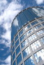 High modern office tower building over cloudy sky bottom up view vertical photo Royalty Free Stock Photo