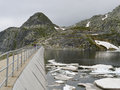 High mountain dam wall in a cold sullen day Royalty Free Stock Photo
