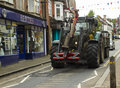 A high powered heavy duty agricultural tractor on the narrow road through an English village.