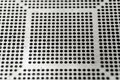 stock image of  Close-up of used laser CNC high precision small pitch cut stencil for BGA chip reballing for electronics industry in partial focus