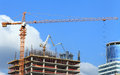 High-rise building under construction with crane and concrete pump. Royalty Free Stock Photo