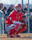 High school baseball catcher watches the dugout Royalty Free Stock Photo