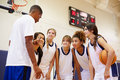 High school basketball team having team talk with coach giving advice Stock Photography