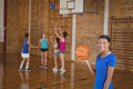 High school girl holding a basketball while team playing in background Royalty Free Stock Photo