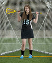 High school girls lacrosse player relaxes with her trusty stick over her shoulder as she poses in front of the goal for an Royalty Free Stock Photography