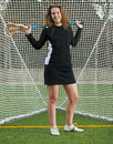 High school girls lacrosse player relaxes with her trusty stick over her shoulder as she poses in front of the goal for an Royalty Free Stock Photos