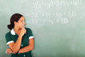 High school maths happy female student in classroom looking at writing on the blackboard Royalty Free Stock Photo