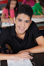 High school student smiling while sitting at desk portrait of male in classroom Royalty Free Stock Image