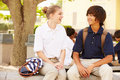 High school students wearing uniforms on school campus smiling at each other Royalty Free Stock Image