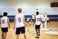 High school volleyball match in gymnasium working as a team Royalty Free Stock Photo