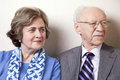 High society senior couple s his s s her late s sitting sofa looking away to right side frame Royalty Free Stock Photos