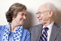 High society senior couple s his s s her late s sitting sofa looking eachother very much love joy Stock Images