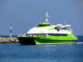 High speed boat a white green arrive to the port of alonissos island greece Royalty Free Stock Photo