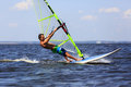 High speed windsurfer young man windsurfing with trailing wake Royalty Free Stock Images