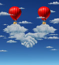 High stakes agreement business concept with two red hot air balloons with businessmen coming together and flying above a group of Royalty Free Stock Images